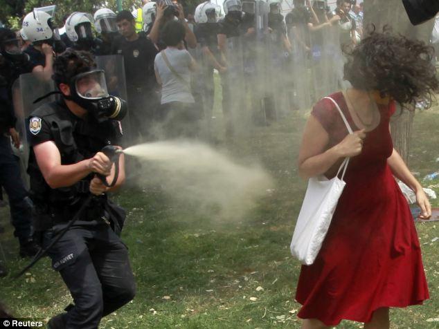"""""""Femeia in roșu"""", cetățean britanic, """"turistă"""" la manifestațiile din piața Taksim, întorcând spatele jetului de gaz lacrimogen, după ce în prealabil a avut grija sa provoace politia turca arătându-le gesturi obscene. Foto - agenția Reuters"""