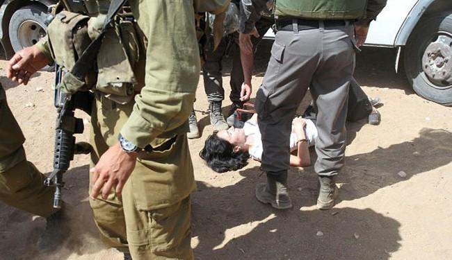 Diplomatul francez Marion Fesneau-Castaing punsă la pământ după ce a fost târâtă de către forțele israeliene de la un camion incarcat cu provizii, pe 20 septembrie 2013, pe un drum care duce la satul West Bank din Khirbet al-Makhul